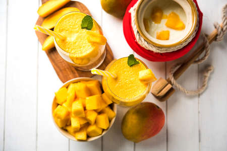 Mango Lassi or smoothie in big glass or small bottles with curd, cut fruit pieces and blender. Moody background, selective focus Stock Photo