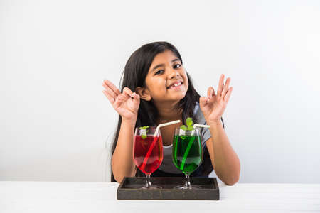 Cute asianIndian little girl posing with cold drink or fresh juice at table over white background