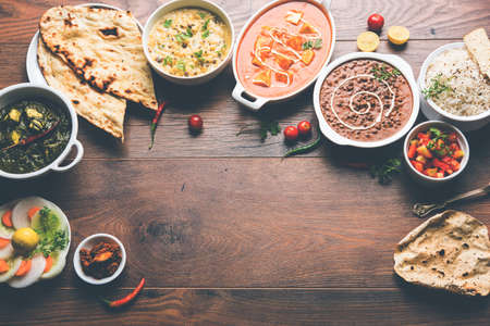 Assorted indian food for lunch or dinner, rice, lentils, paneer, dal makhani, naan, chutney, spices over moody background. selective focus 스톡 콘텐츠