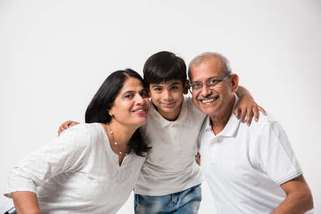 Indian/asian senior couple with grandson, isolated over white