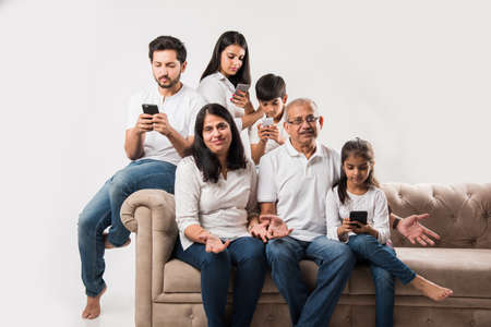 Indian family sitting on couch while senior adults getting bored and young members busy on smartphone Stockfoto