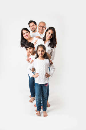 Indian family standing isolated over white background. senior and  young couple with kids wearing white top and blue jeans. Banque d'images