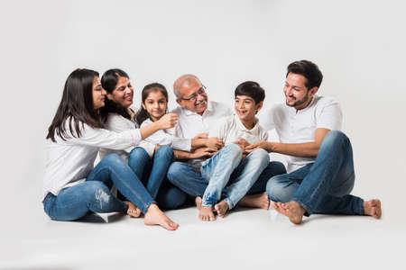 familia india / asiática que se sienta sobre el fondo blanco. Pareja de ancianos y jóvenes con niños vestidos de jeans azul y top blanco. Foto de archivo
