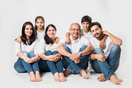 indian/asian family sitting over white background. senior and young couple with kids wearing white top and blue jeans. selective focus Stock fotó