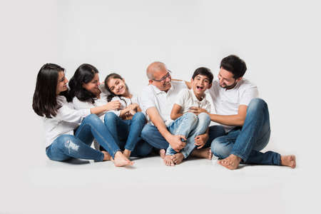 indian/asian family sitting over white background. senior and young couple with kids wearing white top and blue jeans. selective focus Stock Photo