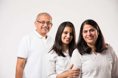 Senior Indian couple with young adult girl standing isolated over white background. selective focus 스톡 콘텐츠