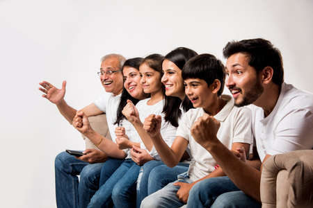 Multi generation Indianasian family watching TV at home while sitting on sofacouch, selective focus 写真素材