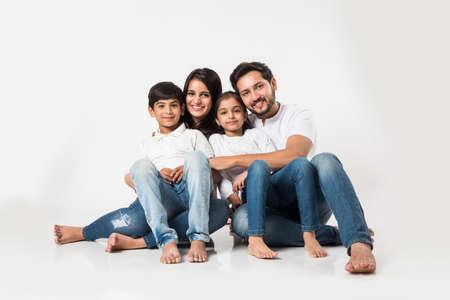 Jeune famille indienne/asiatique assise isolée sur fond blanc. mise au point sélective Banque d'images