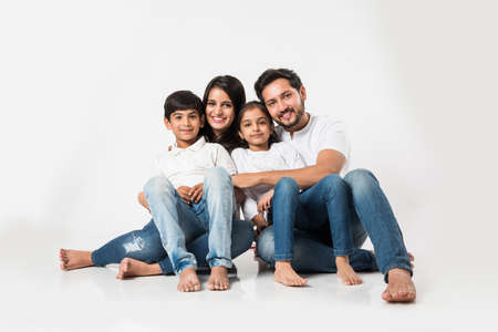 Sentada joven india / asiática de la familia aislada sobre el fondo blanco. enfoque selectivo Foto de archivo