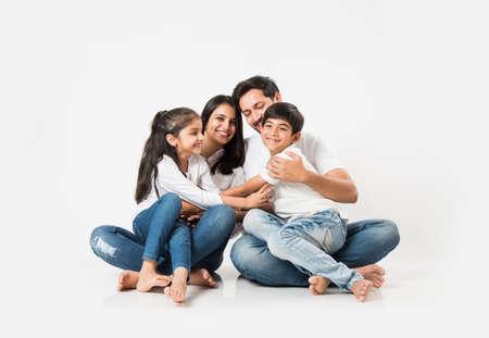 Sentada joven india / asiática de la familia aislada sobre el fondo blanco. enfoque selectivo