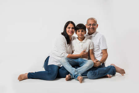 Indianasian senior couple with grandson, isolated over white