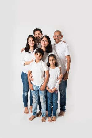 Famille indienne debout isolé sur fond blanc. senior et jeune couple avec enfants portant un haut blanc et un jean bleu. mise au point sélective