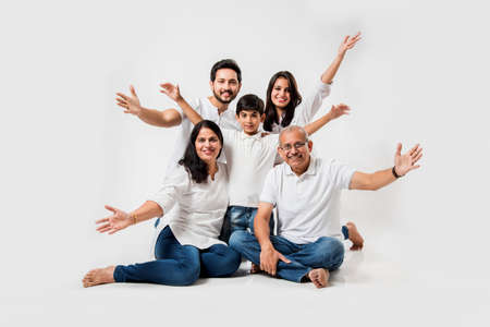indian/asian family sitting over white background. senior and young couple with kids wearing white top and blue jeans. selective focus 免版税图像