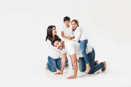 glücklicher verrückter Ritt auf Vaters Rücken. Indisches kleines Mädchen, das auf Papas Rücken sitzt, während Mutter und Bruder lachen. selektiver Fokus