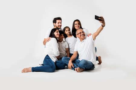 La familia india que toma la foto del selfie con el teléfono inteligente mientras está sentado sobre un fondo blanco incluye 3 generaciones. enfoque selectivo