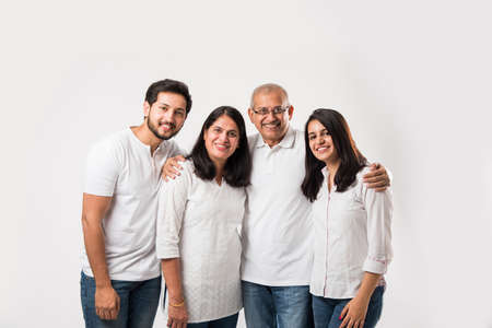 happy Indian family standing isolated over white background. senior parents with young kids wearing white top and blue jeans. selective focus