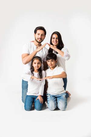 Famille indienne faisant le signe de la maison sur fond blanc. mise au point sélective Banque d'images