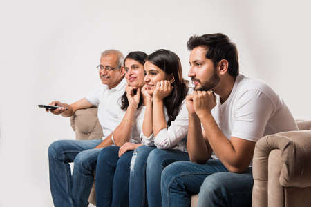 Indian/asian  family watching TV while sitting on sofa/couch Imagens