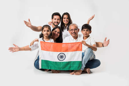 Happy Indian family holding national tricolour flag while sitting isolated over white background, selective focus