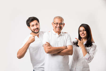 Indian old father embarrassing his young adult kids. Asian family of 3 standing isolated over white background. selective focus