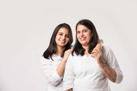 Indian starej matki z młodą córką stojącą odizolowane na białym tle, mając na sobie biały top i niebieskie dżinsy. selektywne skupienie