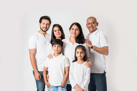 Indian family standing isolated over white background. senior and  young couple with kids wearing white top and blue jeans. selective focus Stock Photo