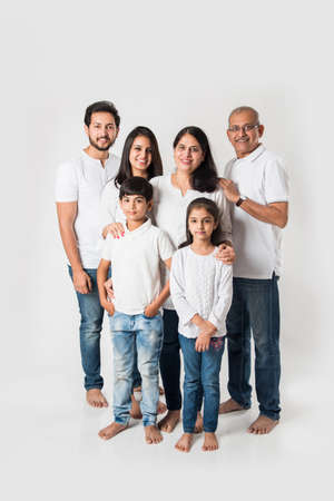 Indian family standing isolated over white background. senior and  young couple with kids wearing white top and blue jeans. selective focus Banque d'images
