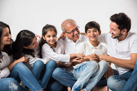 indian/asian family sitting over white background. senior and young couple with kids wearing white top and blue jeans. selective focus Banque d'images