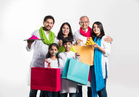 indian family celebrating holi festival with shopping bags, sweet laddu gifts and colours in plate. isolated over white background. selective focus meaning
