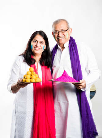 senior couple playing holi, Holding plate full of sweet laddu and colours. isolated over white background