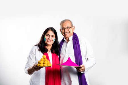 senior couple playing holi, Holding plate full of sweet laddu and colours. isolated over white background
