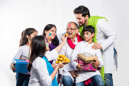 Indian Family celebrating Holi festival with sweet Laddu, gifts and colours in plate. isolated over white background. selective focus