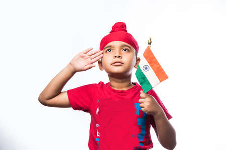 Indian sikhpunjabi little boy holding National Tricolour flag while standing isolated over white Stock Photo
