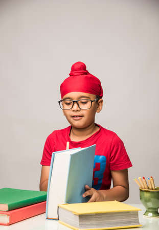 Small Indian/sikh boy studying at study table with books Banco de Imagens