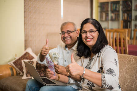 Senior Indian/asian couple accounting, doing home finance and checking bills with laptop, calculator and money while sitting on sofa/couch at home Foto de archivo