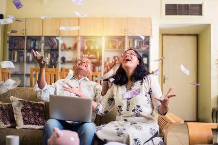Feliz pareja senior indio / asiático habiendo ganado lotería o ganancias de inversión en forma de dinero / papel moneda cayendo del cielo / concepto de lluvia