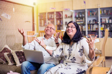 Happy Senior Indian/asian couple having won lottery or investment earning in form of Money/paper currency falling from sky / raining concept 版權商用圖片 - 119504261