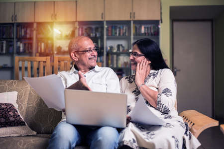 Senior coppia indiana/asiatica contabilità, facendo finanza domestica e controllando le bollette con laptop, calcolatrice e denaro mentre si è seduti sul divano/divano a casa