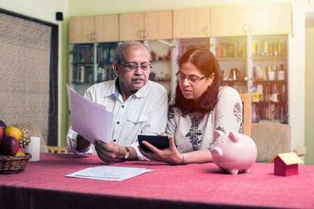 Senior Indian/asian couple accounting, doing home finance and checking bills with laptop, calculator and money while sitting on sofa/couch at home Standard-Bild
