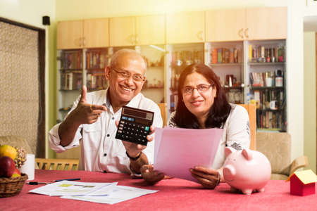 Senior Indianasian couple accounting, doing home finance and checking bills with laptop, calculator and money while sitting on sofacouch at home