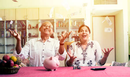 Happy Senior Indianasian couple having won lottery or investment earning in form of Moneypaper currency falling from sky  raining concept