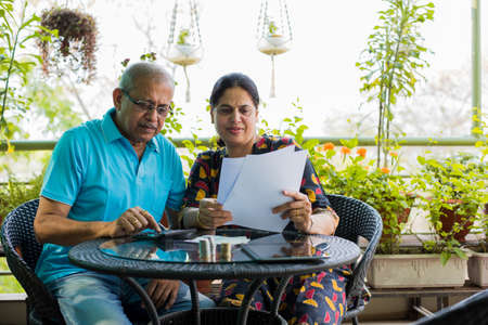 Senior coppia indiana/asiatica contabilità, facendo finanza domestica e controllando le bollette con laptop, calcolatrice e denaro mentre si è seduti sul divano/divano a casa Archivio Fotografico