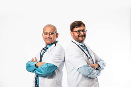 Two Indian/asian male doctors discussing medical case with chart, standing isolated over white background 写真素材
