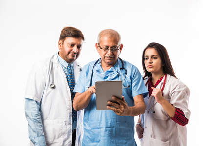 Group of successful Indian medical doctors using tablet wireless computer/technology while standing isolated over white background, selective focus