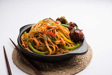 Manchurian Hakka / Schezwan noodles, popular indochinese food served in a bowl. selective focus