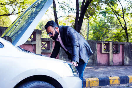 worried Indian Businessman with vehiclecar breakdown, talking on phone