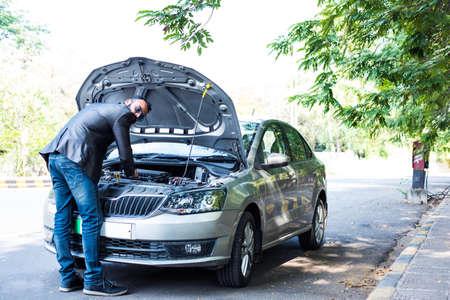 worried Indian Businessman with vehiclecar breakdown, talking on phone