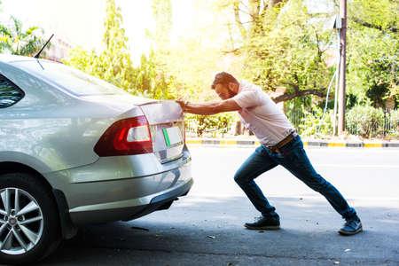 Indischer bärtiger Mann schiebt kaputtes Auto/Fahrzeug mit voller Kraft auf die Straße Standard-Bild