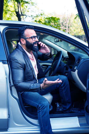 Indian Bearded businessman using smart phone while driving the car  Banco de Imagens