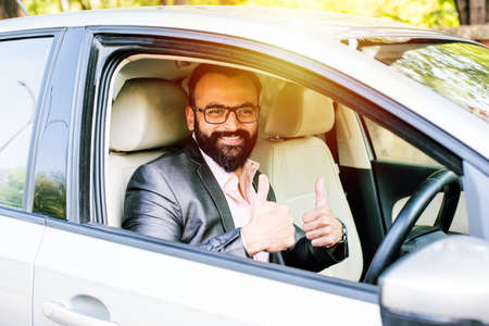 Indian Bearded businessman driving car, selective focus